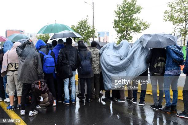 Migrants wait under the rain to be evacuated by bus from a makeshift camp at Porte de la Chapelle in the north of Paris on August 18 2017 More than a...