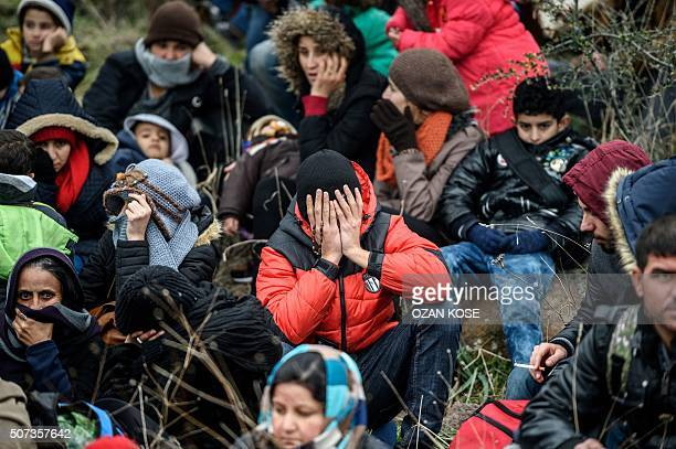 TOPSHOT Migrants wait while they are camping after being cheated by smugglers on January 29 2016 in Kucukkuyu district in Canakkale as they try to...