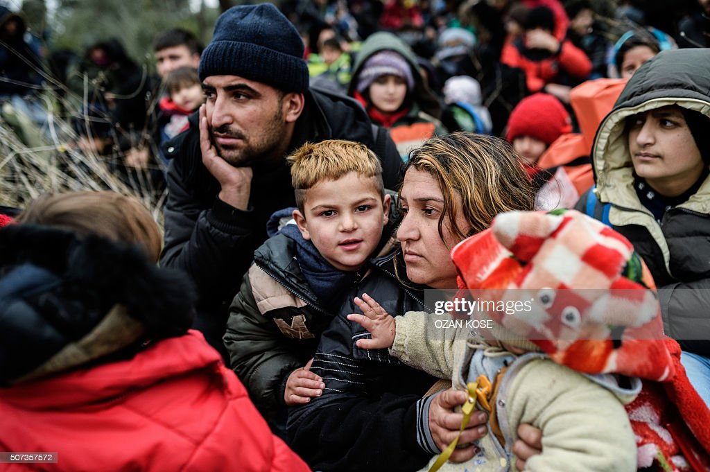TOPSHOT Migrants wait with life vests while they are camping after being cheated by smugglers on January 29 2016 in Kucukkuyu district in Canakkale...