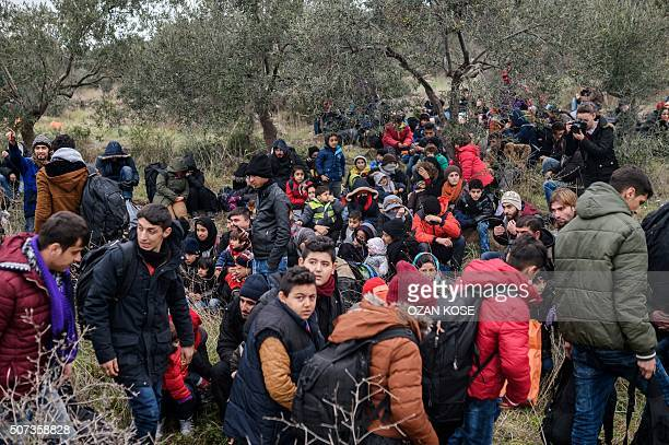 Migrants wait with life vests while they are camping after being cheated by smugglers on January 29 2016 in Kucukkuyu district in Canakkale as they...