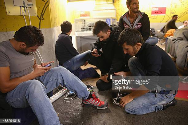 Migrants waiting at Salzburg Hauptbahnhof railway station for available seats on trains to Germany charge their mobile phones in a shelter set up in...