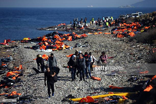 Migrants walk along a beach after making the crossing from Turkey to the Greek island of Lesbos on November 14 2015 in Sikaminias Greece Rafts and...