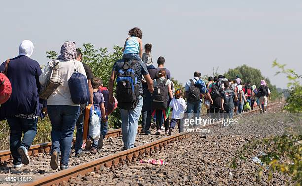 Migrants walk along a railway line after they have crossed the border from Serbia into Hungary close to the village of Roszke on August 30 2015 near...