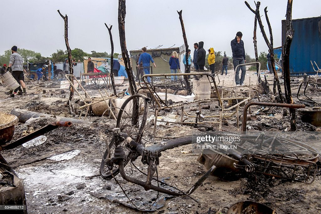 Migrants walk among the burnt tents after a massive brawl that left 40 people injured in the 'Jungle' migrant camp in the northern French town of Calais on May 27, 2016. Some 20 people living in the 'Jungle' refugee camp in the northern French port of Calais were injured in a brawl between around 200 Afghans and Sudanese on May 26, 2016. / AFP / PHILIPPE