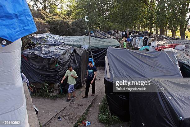 Migrants walk in a make shift camp known as the 'New Jungle' on July 1 2015 in Calais France Crosschannel travel has be disrupted for third day this...