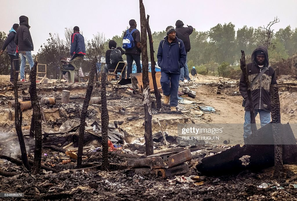 Migrants walk in the middle of burnt shelters after a massive brawl that left 40 people injured in the 'Jungle' migrant camp in the northern French town of Calais on May 27, 2016. Some 20 people living in the 'Jungle' refugee camp in the northern French port of Calais were injured in a brawl between around 200 Afghans and Sudanese on May 26, 2016. / AFP / PHILIPPE