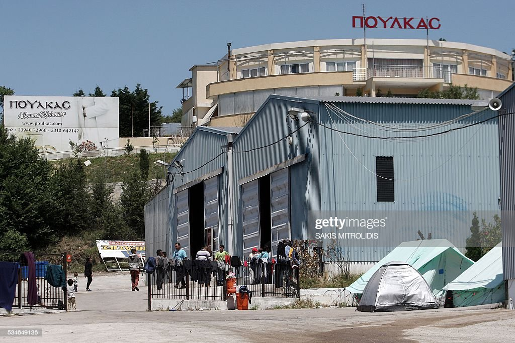 Migrants walk inside a new refugees camp in an abandoned factory in Derveni, a north suburb of Thessaloniki on 27 May, 2016. The squalid Idomeni refugee camp in northern Greece which became a symbol of Europe's migrant crisis has been fully evacuated, police said Thursday, as another 30 died crossing the Mediterranean. In the space of three days, police transferred about 4,000 migrants by bus from Idomeni to newly created camps in the industrial outskirts of Greece's second city Thessaloniki. / AFP / SAKIS