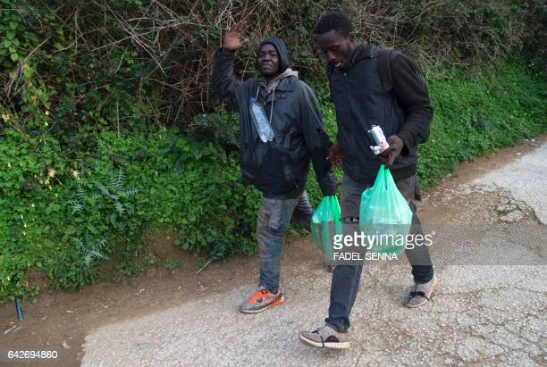 Migrants walk near the forest of the Moroccan city of Fnidek on February 18 2017 after forcing their way through a fence between Morocco and the tiny...