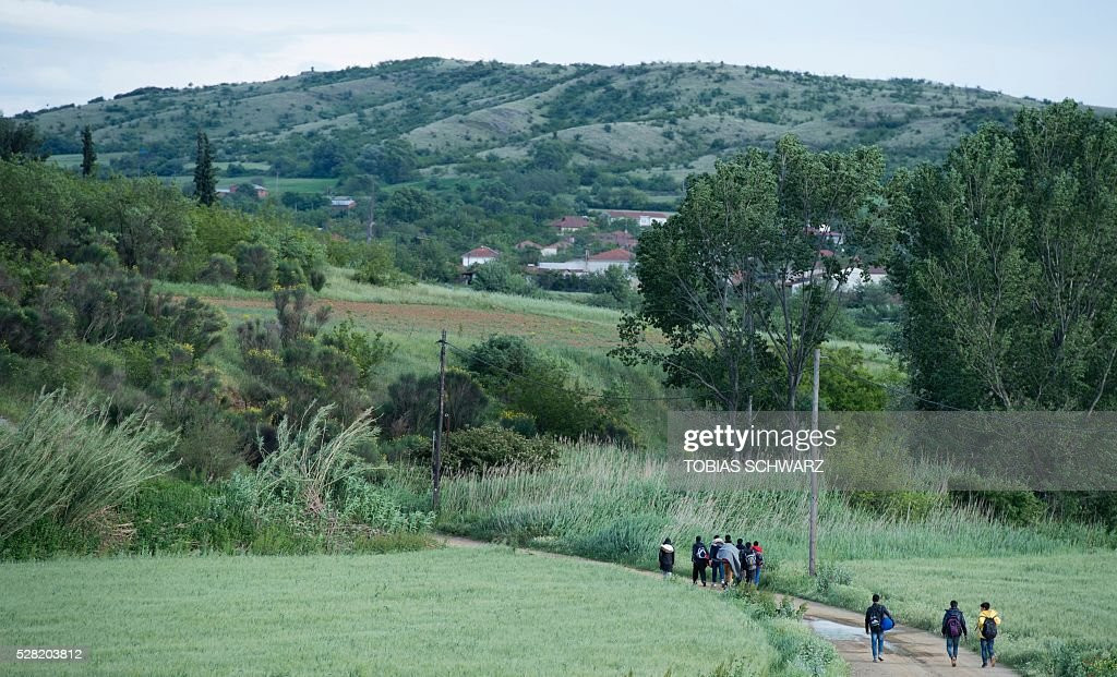 Migrants walk on a road after they had been rejected at the Macedonian border towards a makeshift camp for migrants and refugees near the village of Idomeni not far from the Greek-Macedonian border on May 4, 2016. Some 54,000 people, many of them fleeing the war in Syria, have been stranded on Greek territory since the closure of the migrant route through the Balkans in February. / AFP / TOBIAS