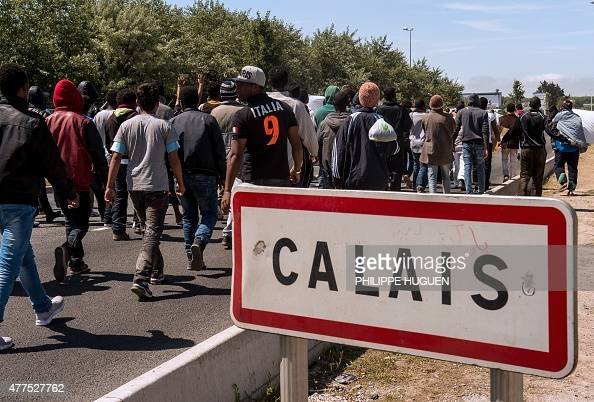 Migrants walk on June 17 2015 towards the ferry port of Calais northern France Around 3000 migrants built makeshift shelters in the socalled 'New...