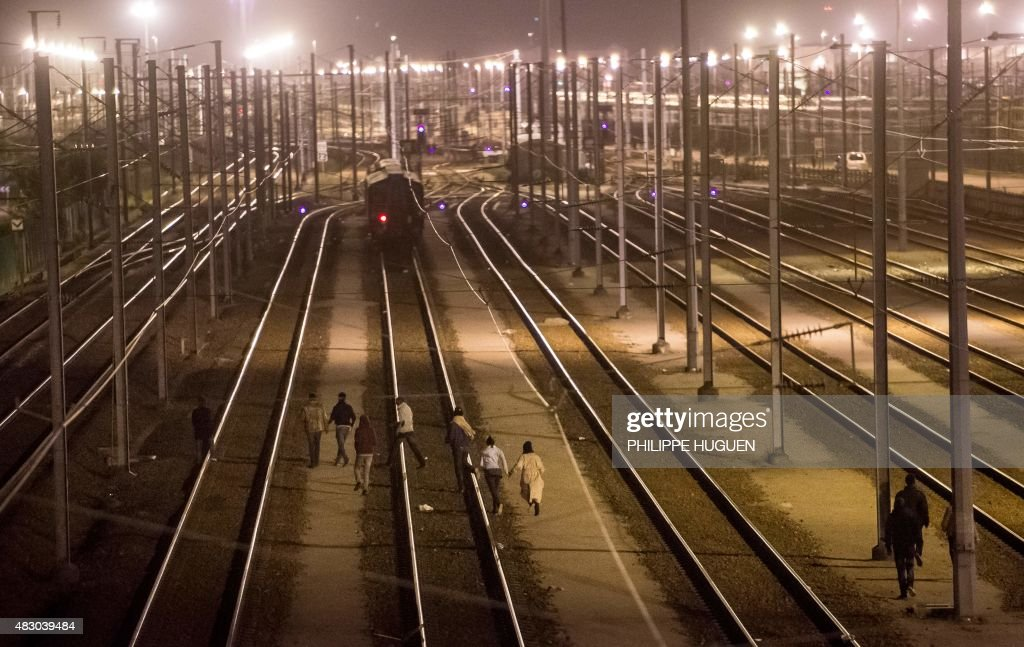 Migrants walk on rail tracks in the Channel Tunnel site in Frethun, northern France, on August 5, 2015. The European Commission offered August 4 to help France and Britain deal with the migrant crisis at the Channel Tunnel, as police on both sides braced for new attempts at the crossing.