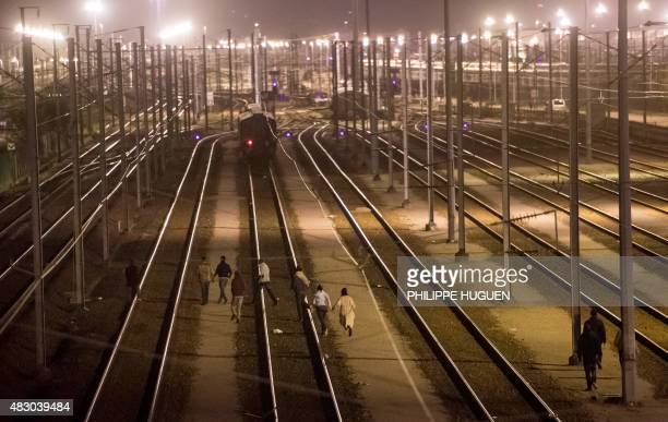 Migrants walk on rail tracks in the Channel Tunnel site in Frethun northern France on August 5 2015 The European Commission offered August 4 to help...