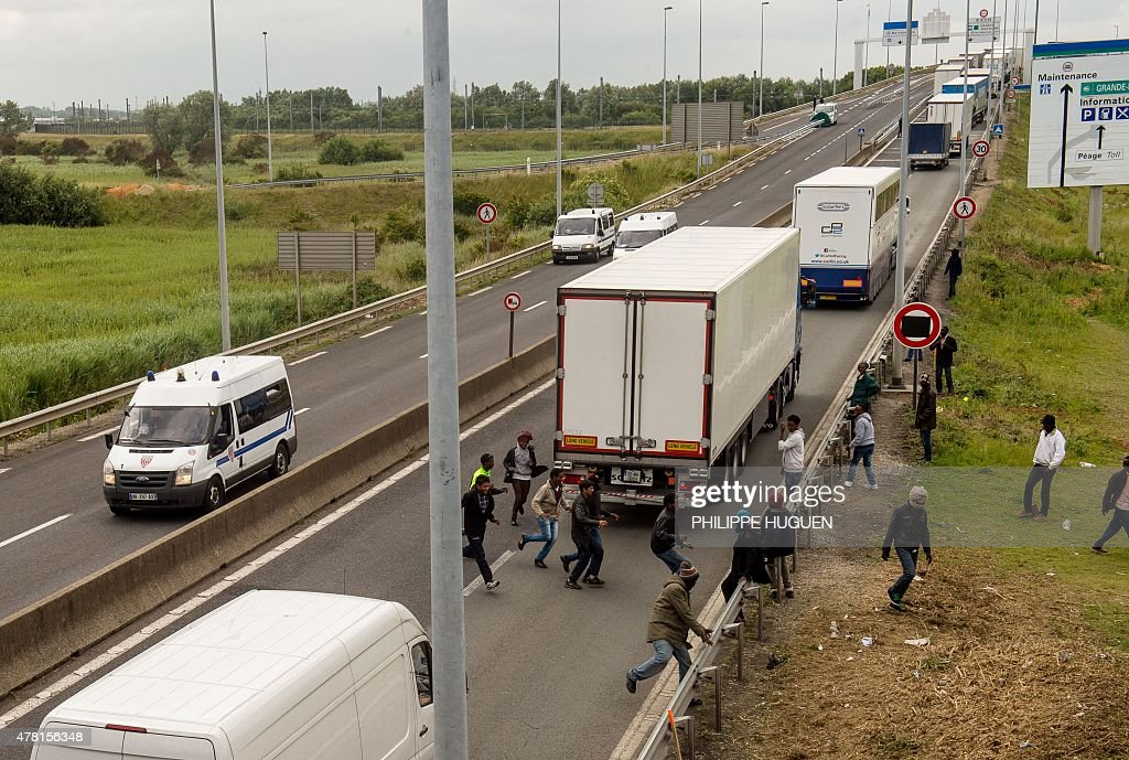 Migrants walk on the A16 highway as they try to access the Channel Tunnel on June 23, 2015 in Calais, northern France.