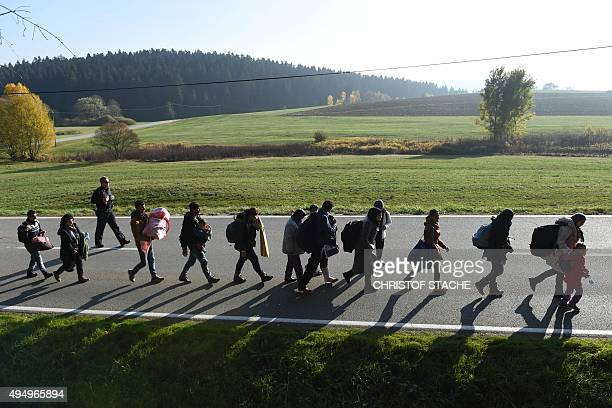 Migrants walk on the road after crossing the AustrianGerman border near the Bavarian village Wegscheid southern Germany on October 30 2015 AFP PHOTO...