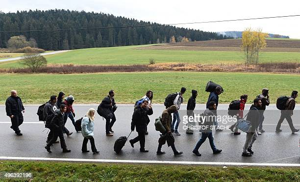 Migrants walk on the road after crossing the AustrianGerman border near the Bavarian village of Wegscheid southern Germany on November 9 2015 AFP...