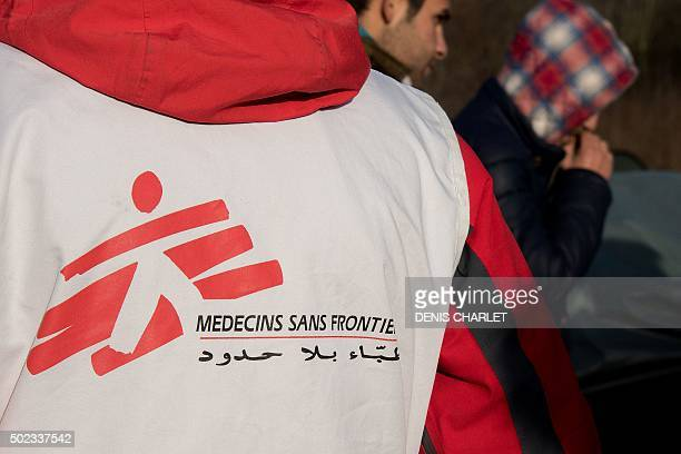 Migrants walk past a Doctors Without Borders volunteer at the Grande Synthe migrant camp near Dunkerque in northern France on December 23 2015 More...