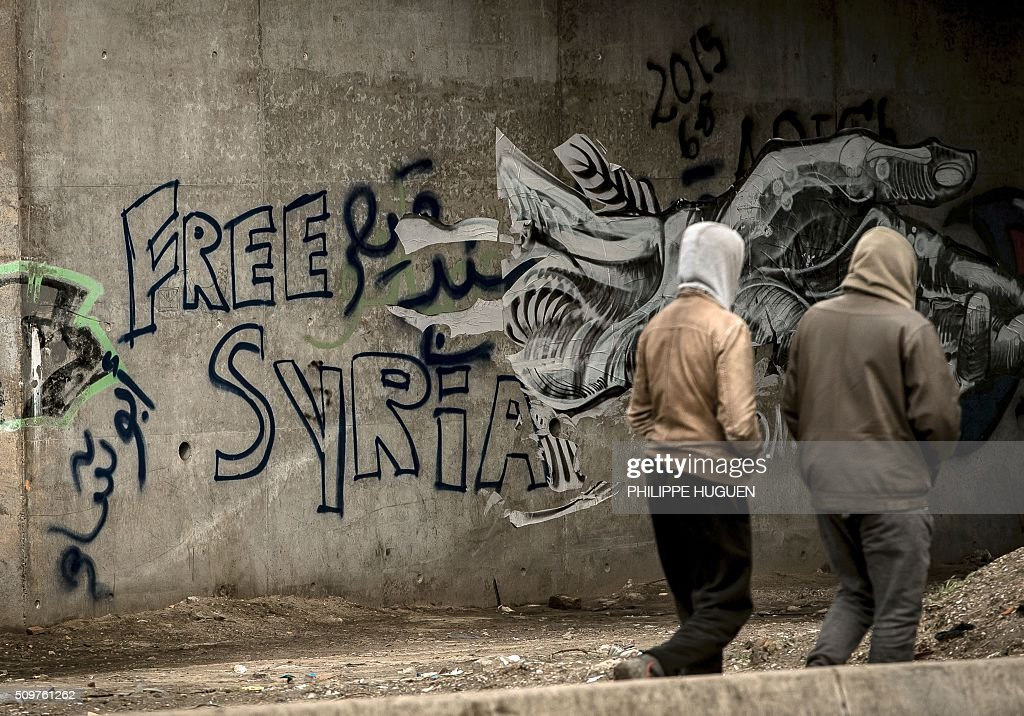 Migrants walk past a graffiti reading 'Free Syria' in the so-called 'Jungle' migrant camp in Calais, northern France, on February 12, 2016. / AFP / PHILIPPE HUGUEN