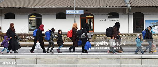 Migrants walk to a train at the central railway station in Passau southern Germany on November 18 2015 AFP PHOTO / CHRISTOF STACHE