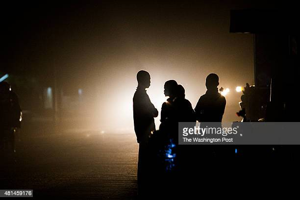 AGADEZ NIGER Migrants walk towards the bus station in Agadez Niger as the lights of a bus arriving from the capital Niamey illuminate the road into...