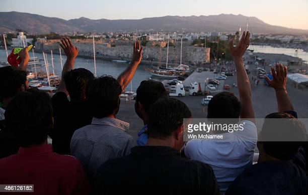 Migrants wave to friends as the Blue Star ferry pulls away from port on the island of Kos headed for the Greek mainland port of Piraeus on August 31...