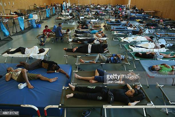 Migrants who had arrived by train to Germany sleep on cots while waiting to register at a center for migrants at a facility of the German Federal...