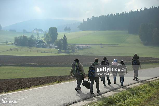 Migrants who had arrived via buses chartered by Austrian authorities walk towards the border to Germany on October 17 2015 near Fuchsoedt Austria...