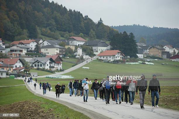 Migrants who had arrived via buses chartered by Austrian authorities walk towards the border to Germany on October 17 2015 near Mistlberg Austria...