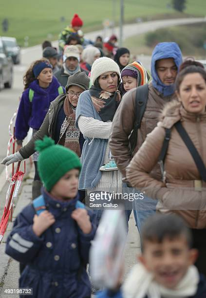 Migrants who had walked across the nearby border from Austria line up to enter a temporary police facility on October 17 2015 in Wegscheid Germany...