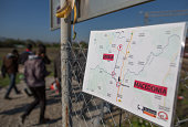Migrants who have arrived on a train from Gevgelija on the Greek border walk past a map and towards the Serbian border on October 25 2015 in...