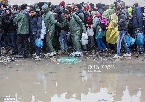 Migrants who have just arrived from Greece walk through rain water puddles as they make their way to a shelter tent in a refugee reception centre on...