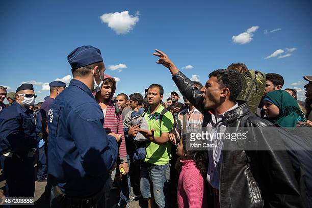 Migrants who have just crossed into Hungary argue with the police as they wait for buses to take them to a reception camp on September 7 2015 in...