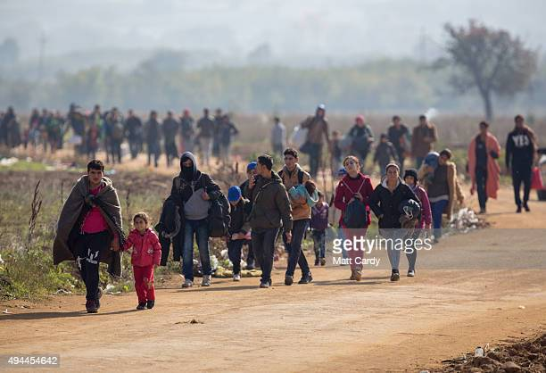 Migrants who have just crossed the border with Macedonia walk towards the village of Miratovac on October 27 2015 in Preshevo Serbia Despite the...