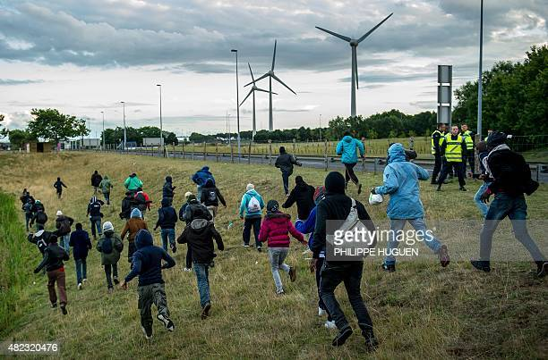Migrants who managed to pass the police block on the Eurotunnel site make their way towards the boarding docks in Coquelles near Calais northern...