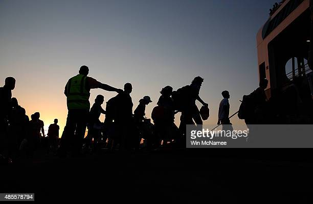 Migrants who recently arrived in Greece and received their immigration papers board a ferry bound for Athens August 28 2015 in Kos Greece Migrants...