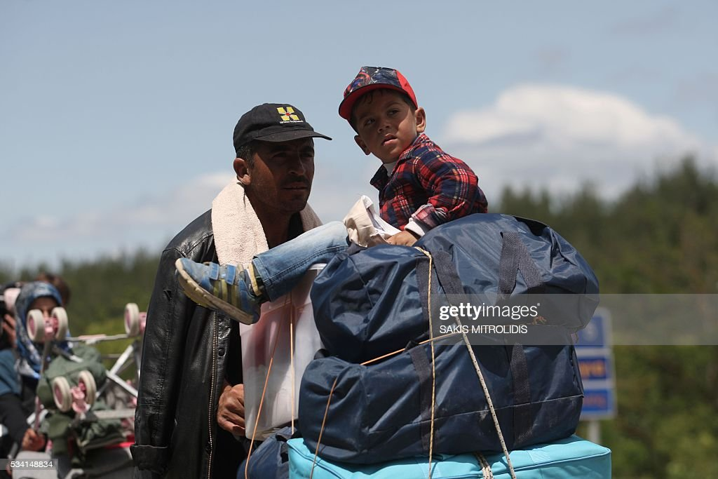 Migrants with their families and belongings leave on foot the Idomeni camp along the Greek-Macedonian border because they do not want to be bussed to another camp on May 25, 2016. In an operation which began shortly after sunrise on May 24, hundreds of Greek police began evacuating the sprawling camp which is currently home to 8,400 refugees and migrants, among them many families with children, an AFP correspondent said. At its height, there were more than 12,000 people crammed into the site, many of them fleeing war, persecution and poverty in the Middle East and Asia, with the camp exploding in size since Balkan states began closing their borders in mid February in a bid to stem the human tide seeking passage to northern Europe. / AFP / SAKIS