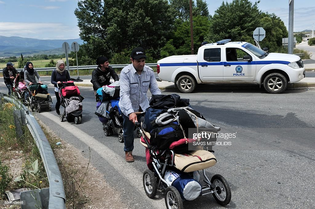 Migrants with their families leave on foot the Idomeni camp along Greek - Macedonian border because they do not want to be bussed to another camp on May 25, 2016. In an operation which began shortly after sunrise on May 24, hundreds of Greek police began evacuating the sprawling camp which is currently home to 8,400 refugees and migrants, among them many families with children, an AFP correspondent said. At its height, there were more than 12,000 people crammed into the site, many of them fleeing war, persecution and poverty in the Middle East and Asia, with the camp exploding in size since Balkan states began closing their borders in mid February in a bid to stem the human tide seeking passage to northern Europe. / AFP / SAKIS