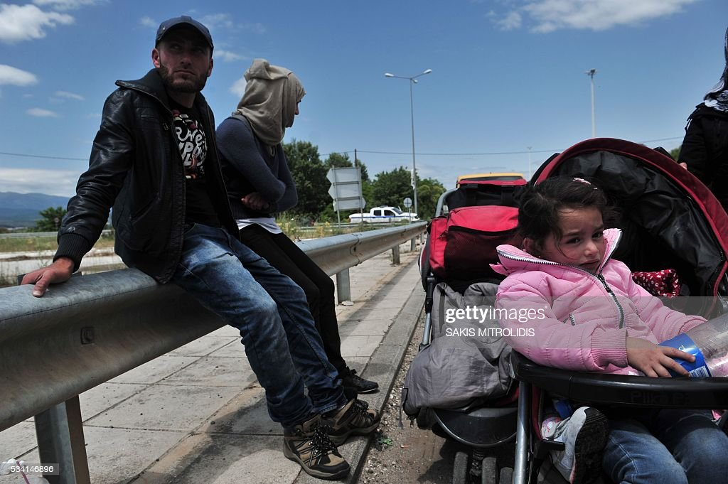 Migrants with their families leave on foot the Idomeni camp along the Greek-Macedonian border because they do not want to be bussed to another camp on May 25, 2016. In an operation which began shortly after sunrise on May 24, hundreds of Greek police began evacuating the sprawling camp which is currently home to 8,400 refugees and migrants, among them many families with children, an AFP correspondent said. At its height, there were more than 12,000 people crammed into the site, many of them fleeing war, persecution and poverty in the Middle East and Asia, with the camp exploding in size since Balkan states began closing their borders in mid February in a bid to stem the human tide seeking passage to northern Europe. / AFP / SAKIS