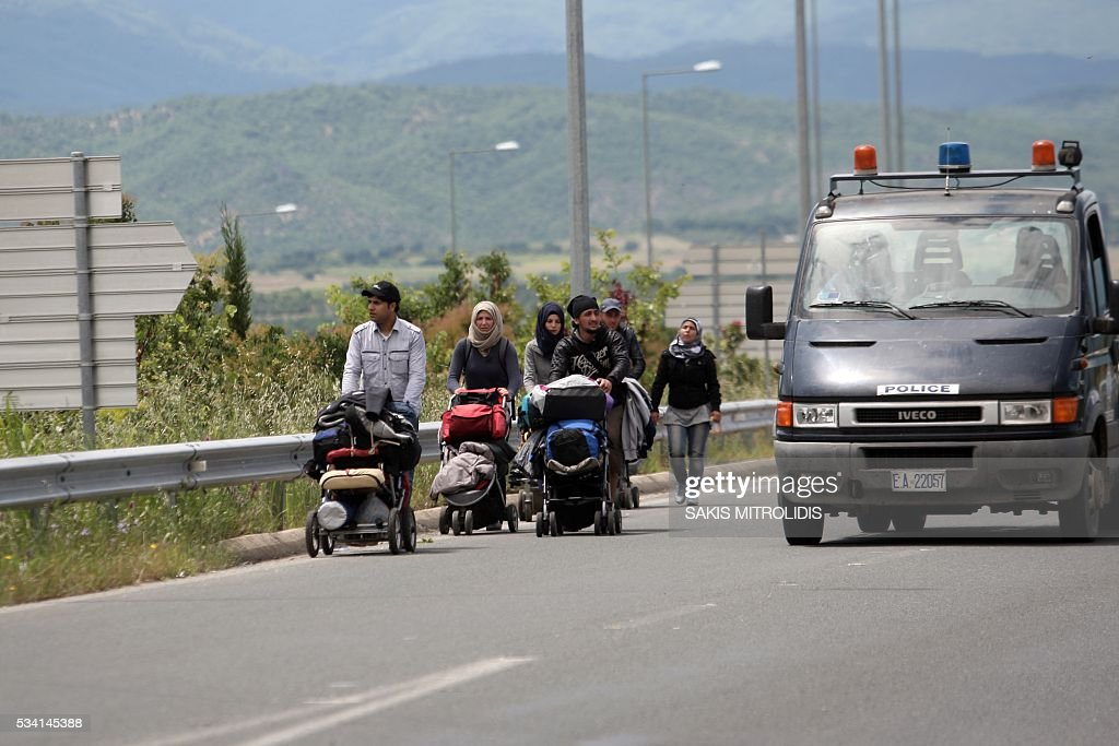 Migrants with their families leave the Idomeni camp along Greek - Macedonian border because they do not want to be bussed to another camp on May 25, 2016. In an operation which began shortly after sunrise on May 24, hundreds of Greek police began evacuating the sprawling camp which is currently home to 8,400 refugees and migrants, among them many families with children, an AFP correspondent said. At its height, there were more than 12,000 people crammed into the site, many of them fleeing war, persecution and poverty in the Middle East and Asia, with the camp exploding in size since Balkan states began closing their borders in mid February in a bid to stem the human tide seeking passage to northern Europe. / AFP / SAKIS