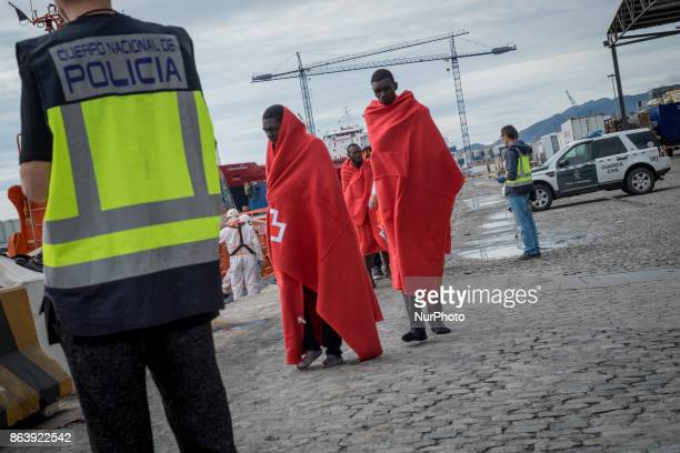 Migrants wrapped in a Red Cross blanket walks after arriving on a Spanish coast guard vessel into the southern Spanish port of Malaga on October 20...