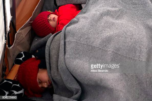 Migrants wrapped in blankets try to keep warm as they wait at a registration camp in the southern Serbian town of Presevo on January 22 2016 in...