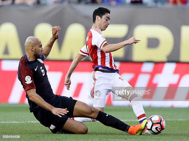 Miguel Almiron of Paraguay tries to keep the ball as John Brooks of United States slides in the first half during the Copa America Centenario Group C...