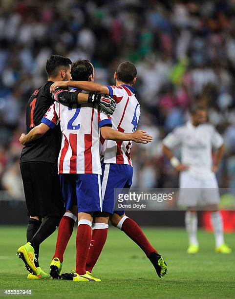 Miguel Angel Moya Diego Godin and Mario Suarez of Atletico de Madrid celebrate with after beating Real Madrid 21 in the La Liga match between Real...