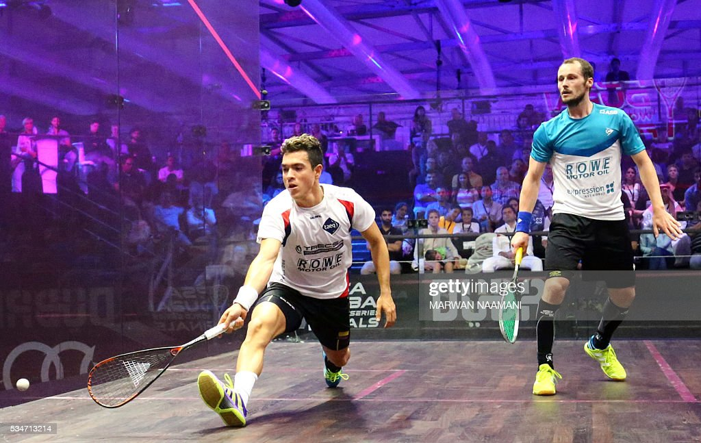 Miguel Angel Rodriguez (L) of Colombia plays a backhand to Gregory Gaultier of France during their semi-final match of the Dubai PSA World Series Finals squash tournament in Dubai on May 27, 2016. / AFP / MARWAN