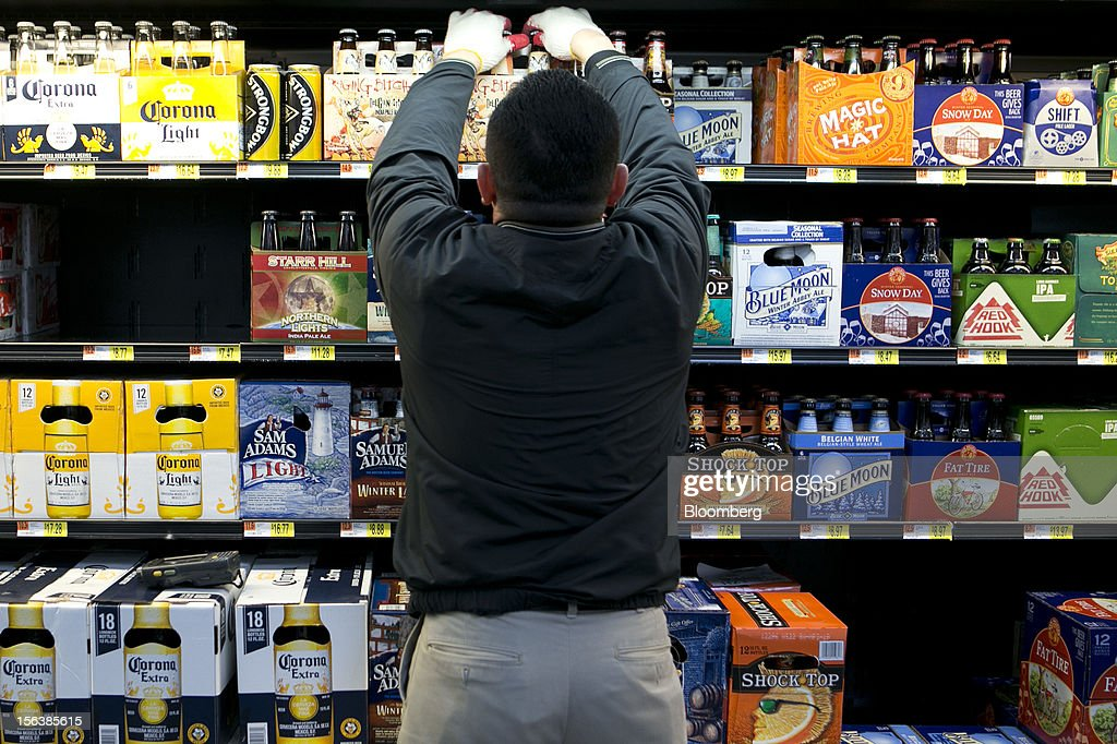 Miguel Bustillo stocks the beer cooler at a Wal-Mart store in Alexandria, Virginia, U.S., on Wednesday, Nov. 14, 2012. Wal-Mart Stores Inc. is scheduled to release earnings data on Nov. 15. Photographer: Andrew Harrer/Bloomberg via Getty Images