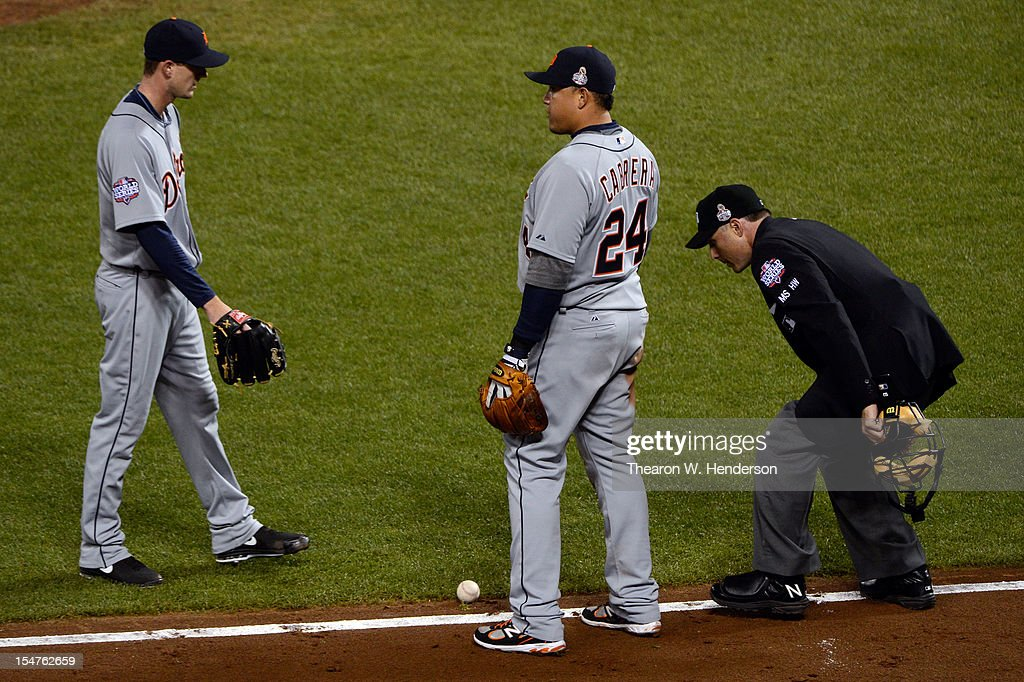 Miguel Cabrera #24 (C) and Drew Smyly #33 of the Detroit Tigers wait to see if the ball goes foul on a bunt single by Gregor Blanco #7 of the San Francisco Giants in the seventh inning as home plate umpire Dan Iassogna watches the play during Game Two of the Major League Baseball World Series at AT&T Park on October 25, 2012 in San Francisco, California.