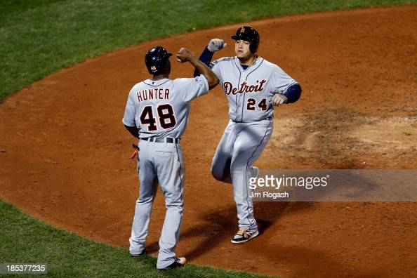 Miguel Cabrera and Torii Hunter of the Detroit Tigers celebrate scoring on Victor Martinez hit a single to deep left center against Franklin Morales...