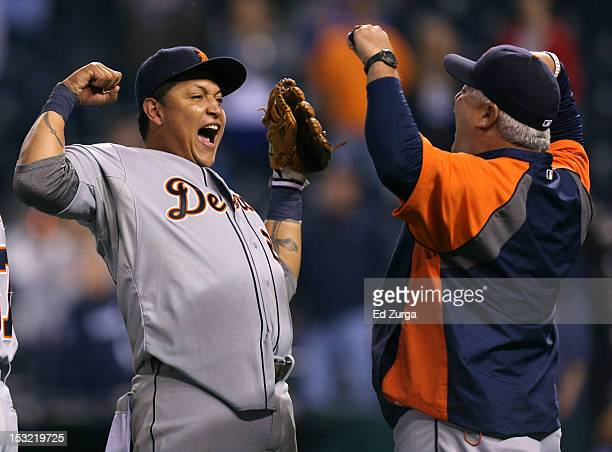 Miguel Cabrera of the Detroit Tigers and bullpen coach Mike Rojas celebrate after winning the American League Central title at Kauffman Stadium on...
