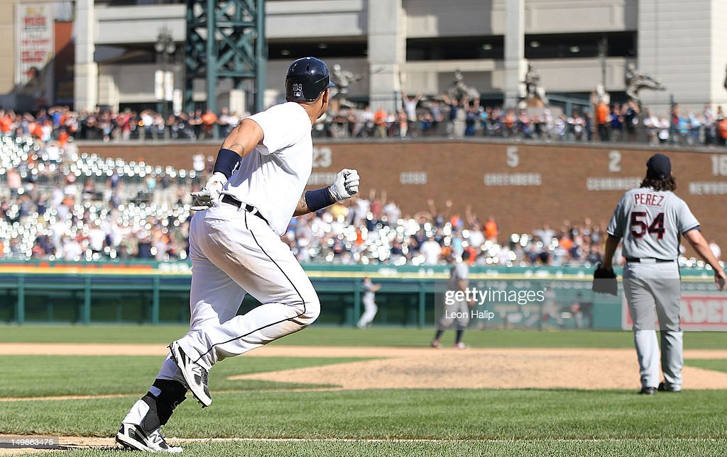 Miguel Cabrera #24 of the Detroit Tigers and Chris Perez #54 of the Cleveland Indians watch the ball clear the left field fence in the tenth inning scoring Omar Infante #4 to give the Tigers a 10-8 win over the Cleveland Indians at Comerica Park on August 5, 2012 in Detroit, Michigan. The Tigers defeated the Indians 10-8.