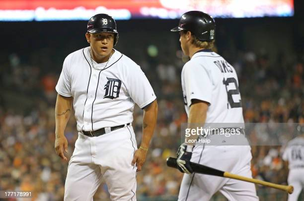 Miguel Cabrera of the Detroit Tigers celebrates with teammate Andy Dirks after scoring on the double to right field by Victor Martines during the...