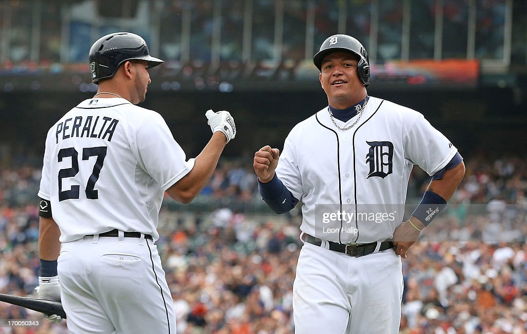 <a gi-track='captionPersonalityLinkClicked' href=/galleries/search?phrase=Miguel+Cabrera&family=editorial&specificpeople=202141 ng-click='$event.stopPropagation()'>Miguel Cabrera</a> #24 of the Detroit Tigers celebrates with teammate <a gi-track='captionPersonalityLinkClicked' href=/galleries/search?phrase=Jhonny+Peralta&family=editorial&specificpeople=213286 ng-click='$event.stopPropagation()'>Jhonny Peralta</a> #27 after scoring on the Victor Martinez #41 single to left field in the seventh inning at Comerica Park on June 6, 2013 in Detroit, Michigan. The Tigers defeated the Rays 5-2.